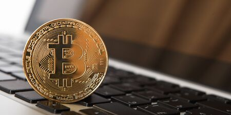 Golden Bitcoin - New virtual money on notebook. A visual representation of digital cryptocurrencies. Bitcoin are fully dematerialized and decentralized electronic currencies. Shallow depth of field. Stock fotó