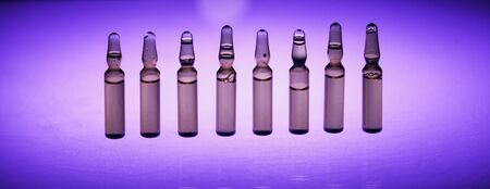 Group object of liquid medicinal agent in limpid glassware in medical laboratory. Ampoules with cosmetic tools, collagen or vitamins