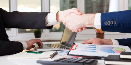 Business people shaking hands finishing up a meeting handshake. Marketing strategy brainstorming. Paperwork and digital in office. Stock Photo
