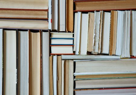 Many Books Piles. Hardback books on wooden table. Books stack texture and background. Back to school. Copy space.