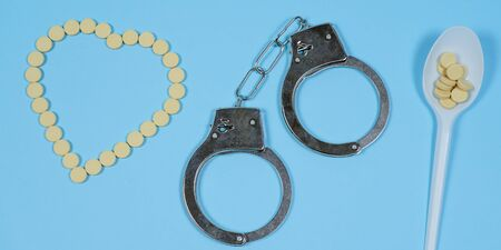 Pills on a blue background whith spoon and handcuffs. Copy spase, spase for text. Banco de Imagens