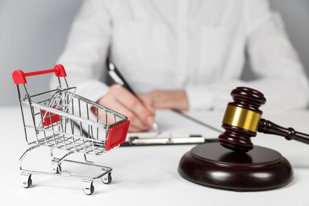 Shopping cart and auction hammer on the background of a lawyer