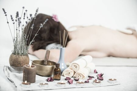Beautiful girl in spa salon. Adult woman having hot stone massage in spa salon. Beauty treatment concept.