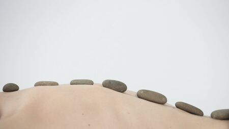 Close up view of spa procedure on color back. Hot stone massage therapy at beauty center.