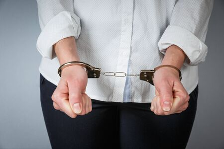 Close-up. Arrested man handcuffed hands at the back isolated on gray background. Prisoner or arrested close-up of hands in handcuffs. Banque d'images
