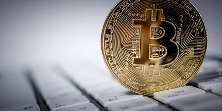 New virtual money Golden bitcoin coin on a white keyboard. Cryptocurrency. Business and Trading concept.