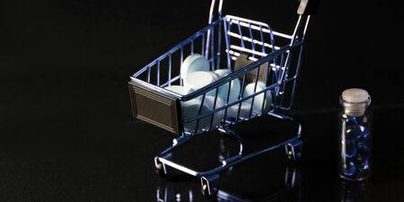 Medications and a gold shopping cart in the concept of expensive medicine. With copy space.