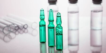 Group of vials with medication on blue methacrylate table. Horizontal composition.