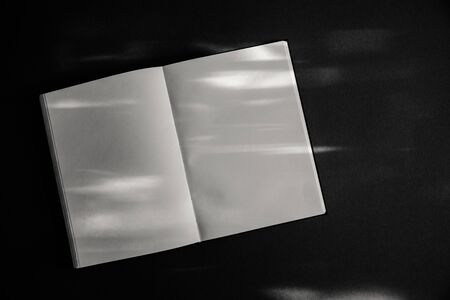 An open book on a table with spots of sunlight. Copy space Stockfoto