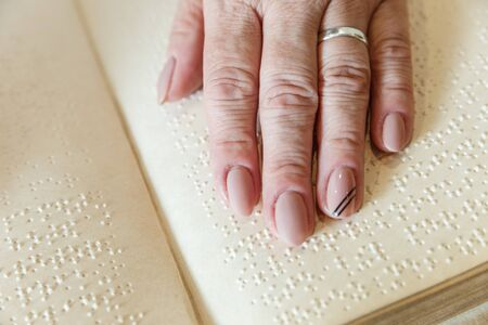 close up view of woman reading braille text on old book