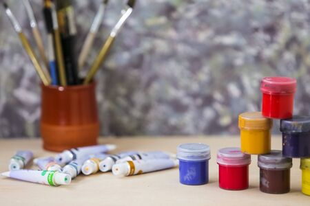 Different colorful brushes on the table, wooden background. Clean painter workplace ready for drawing.