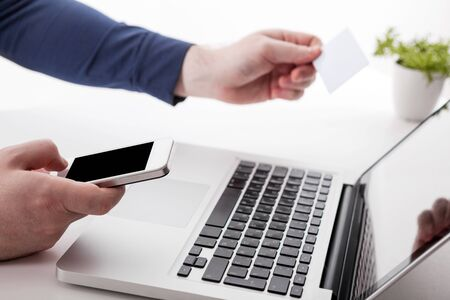 Business man hands using laptop, smartphone and holding credit card working in the office as Online shopping concept