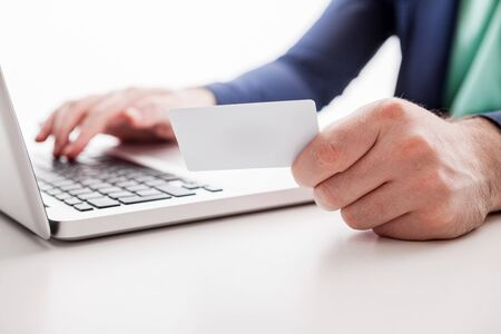 Business man hands using laptop, smartphone and holding credit card working in the office. Business documents on office table  and  with social network diagram as Online shopping concept