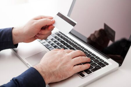 Business man hands holding a credit card and using laptop for online shopping. Online shopping concept.