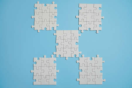 Fragment of a folded white jigsaw puzzle and a pile of uncombed puzzle elements against the background of blue surface.