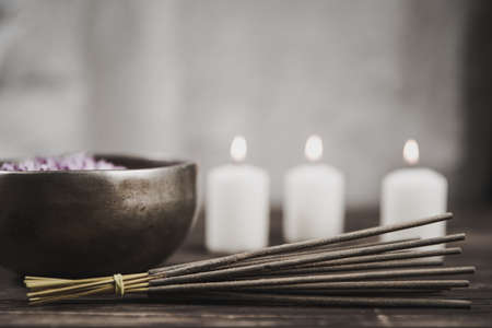 Singing bowl with candles with pebbles on dark wooden background