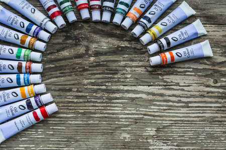 Paint tubes, brushes for painting and palette knifes on old wooden background. Imagens