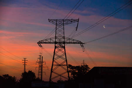 Electrical lines under a night sky with moon. power electric line and transmission tower