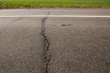 Old asphalt road. Driving on an empty road. Cracked white line on the asphalt road. Shallow depth of field.