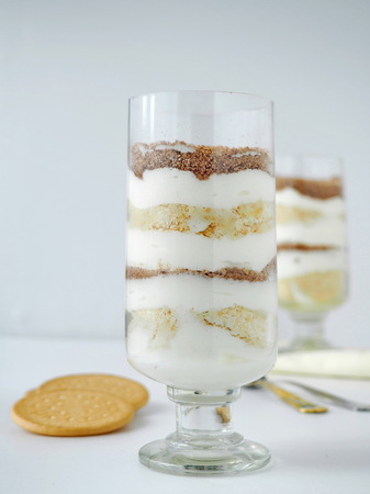 Layered Pudding with Whipped Cream and Biscuits in Tumblers