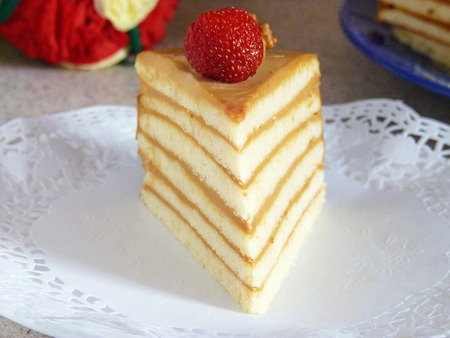 condensed: Piece of Layered Sponge Cake Decorated with Strawberry and Walnut Stock Photo