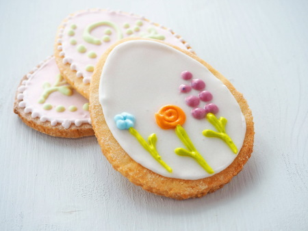 Three easter sugar cookies decorated with royal icing. Ester treat upon wooden table. Beautiful biscuits in the shape of easter egg. Selective focus.