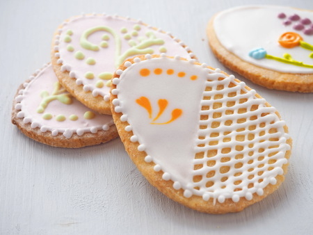 Pile of Easter sugar cookies glazed with royal icing. Ester treat upon rustic table. Beautiful biscuits in the shape of easter egg. Selective focus.