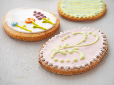 gingerbread: Easter sugar cookies with floral ornament. Homemade cookies glazed with royal icing. Ester treat upon rustic table. Beautiful biscuits in the shape of easter egg. Selective focus.
