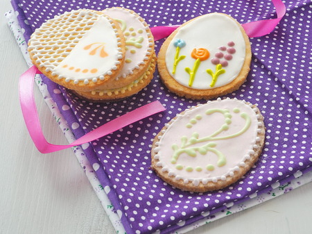gingerbread: Easter sugar cookies with floral ornament. Homemade cookies decorated in the shape of easter egg. Beautiful biscuits upon rustic table with pink ribbon. Selective focus. Stock Photo