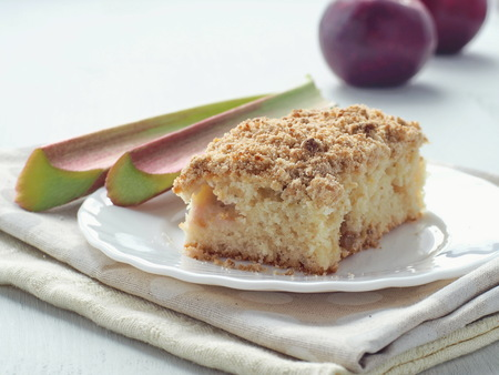 Crumble cake decorated with fresh rhubarb stems and red apples. Homemade pudding. Selective focus.