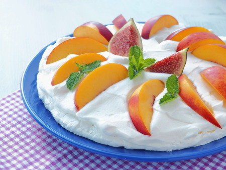 Meringue dessert with figs and peaches. Pavlova cake with whipped cream. Selective focus. Close up.