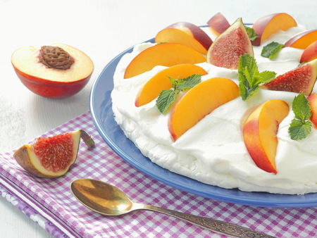 Summer cake with fruits and whipped cream. Meringue dessert. Selective focus. Close up.