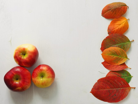 Autumn leaves and red apples on white wooden background. Copy space for your text.