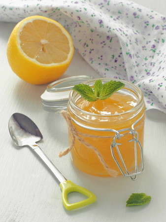 Glass jar full of lemon curd with cute spoon on rustic table. Vertical. Selective focus.