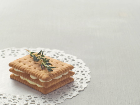 Food background. Homemade cookie with custard cream filling on the bottom left corner of the wooden table. Copy space for your text. Selective focus.