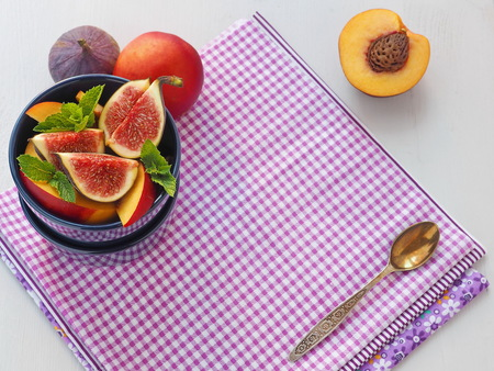 Purple background. Healthy eating concept. Fruit salad in a blue vase. Copy space for your text. Selective focus. Top view. Stock Photo