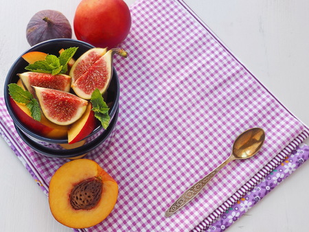 Purple background. Fruit salad in a blue vase with fresh fruits. Copy space for your text. Selective focus. Top view. 写真素材