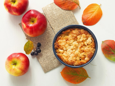 Autumn fruits cake. Homemade crumble with red apples and rowanberry, decorated with bright leaves. Selective focus.