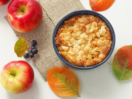 Apple crumble pie. Composition with colorful leaves and apples. Top view. Selective focus. Standard-Bild