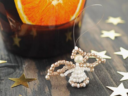 Christmas tree decoration. Little angel made with beads. Handmade ornament. Selective focus.