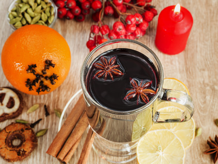 Mulled wine with spices on wooden table sample text photo
