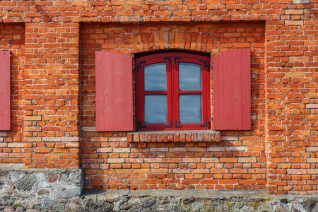 overbuilding: frammento del muro di mattoni rossi con finestra e persiane