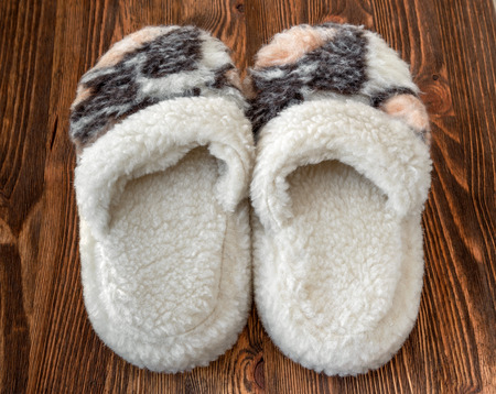 sheep wool: Home slippers made of sheep wool on a wooden background Stock Photo