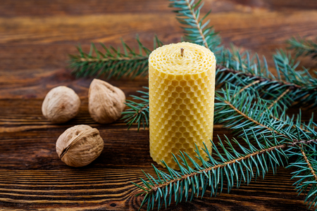 Candle made of natural wax on a wooden background