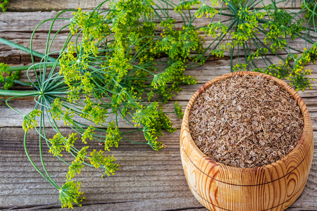 Seeds of dill in a keg on a wooden background Foto de archivo