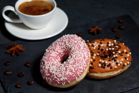 Two donuts and a cup of coffee on a dark gray background