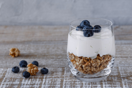 Granola with yogurt and blueberries in a glass beaker on a wooden background
