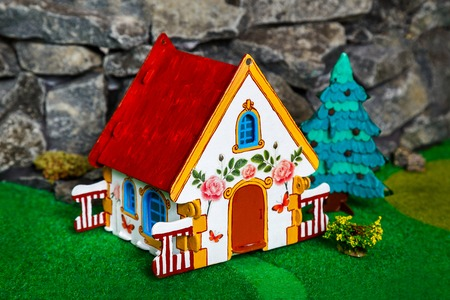 Cardboard house on a toy landscape, on artificial green grass