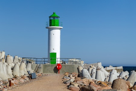 White lighthouse tower on blue sky background, Ventspils, Latvia Imagens