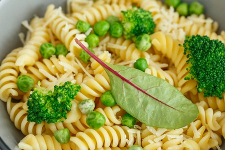 Pasta with green vegetables and parmesan cheese. Vegan fusilli pasta salad with broccoli and green peas